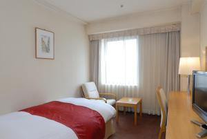 A bed or beds in a room at Yamazaki Seipan Pension Fund Hall