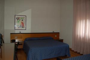 A bed or beds in a room at Hotel Nuova Grosseto