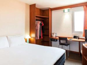 A bed or beds in a room at ibis Douala