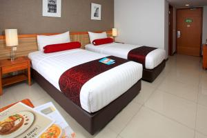 A bed or beds in a room at Ivory Hotel Bandung