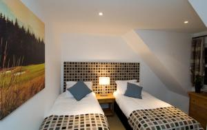 A bed or beds in a room at Inchmarlo Resort & Self-catering Accommodation