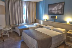 A bed or beds in a room at Hotel Gracher Praia