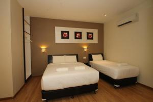A bed or beds in a room at Ipoh Boutique Hotel