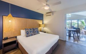 A bed or beds in a room at The Sebel Palm Cove Coral Coast