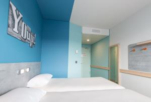 A bed or beds in a room at ibis budget Geneve Palexpo Aeroport