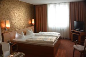Ein Bett oder Betten in einem Zimmer der Unterkunft Atrium Hotel Krüger
