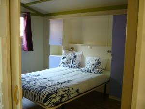 A bed or beds in a room at Camping de l'Amitié