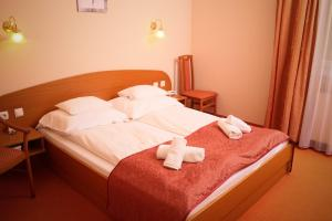 A bed or beds in a room at Thermál Panzió