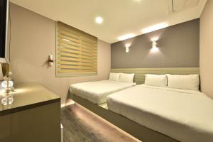 A bed or beds in a room at With U Hotel & Guesthouse