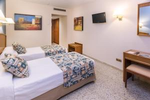A bed or beds in a room at GHT Oasis Park & Spa