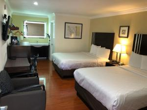 A bed or beds in a room at Lombard Plaza Motel