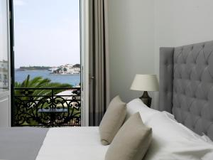 A bed or beds in a room at Poseidonion Grand Hotel