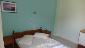 A bed or beds in a room at Poros House Hotel