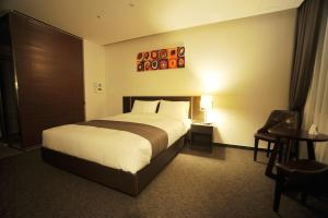 A bed or beds in a room at Yongin Central Co-op Hotel