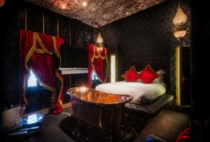 A bed or beds in a room at Crazy Bear Beaconsfield