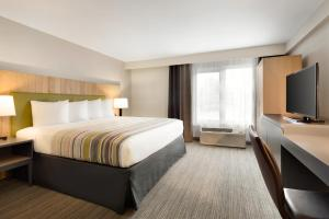 A bed or beds in a room at Country Inn & Suites by Radisson, Seattle-Tacoma International Airport, WA