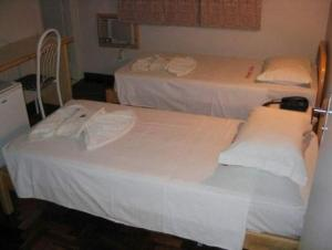 A bed or beds in a room at Hotel Topazio Ltda