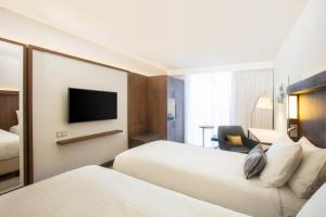 A bed or beds in a room at Courtyard By Marriott Edinburgh West
