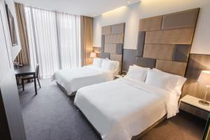 A bed or beds in a room at GHL Hotel Bioxury