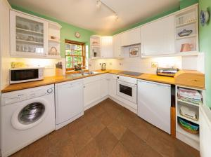 A kitchen or kitchenette at Flowers of May Cottage