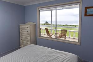 A bed or beds in a room at Seascape Beach House