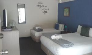 A bed or beds in a room at Woodlands Motel