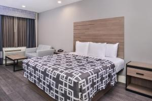 A bed or beds in a room at Palace Inn Blue Tomball Parkway