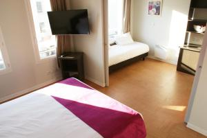 A bed or beds in a room at ApartHotel Sainte-Marthe
