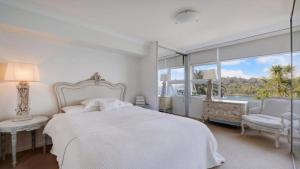 A bed or beds in a room at Elegant Waterfront Apartment in Mosman Bay RAG10