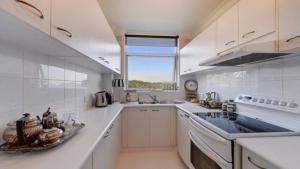 A kitchen or kitchenette at Elegant Waterfront Apartment in Mosman Bay RAG10