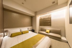 Een bed of bedden in een kamer bij The Rise Osaka Kitashinchi