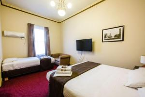 A bed or beds in a room at The Glenferrie Hotel Hawthorn