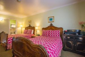 A bed or beds in a room at Carmel Inn & Suites