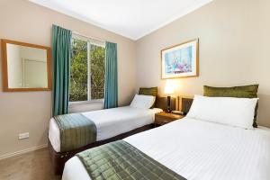 A bed or beds in a room at Punt Road Apartment Hotel