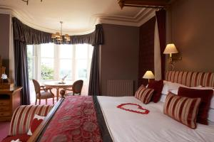 A bed or beds in a room at Loch Ness Country House Hotel