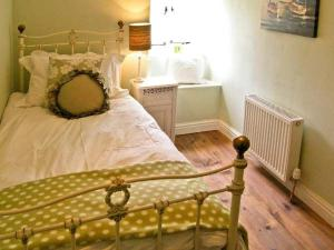 A bed or beds in a room at Quaker Cottage
