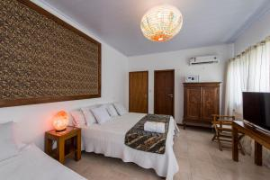A bed or beds in a room at Casa Petunia Pousada Boutique