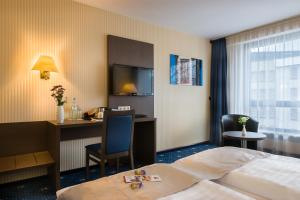 A television and/or entertainment centre at Novum Hotel Imperial Frankfurt Messe