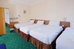 A bed or beds in a room at The Bournemouth Maemar Hotel