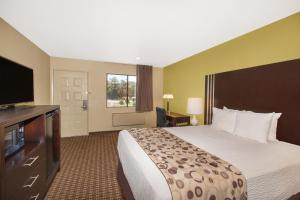 A bed or beds in a room at Days Inn by Wyndham San Jose Airport