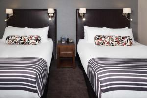 A bed or beds in a room at Sandman Signature Edmonton South Hotel
