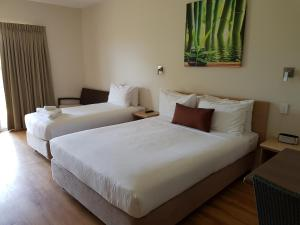 A bed or beds in a room at Club Tropical Resort Darwin