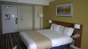 A bed or beds in a room at Holiday Inn Birmingham M6 J7