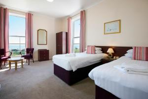 A bed or beds in a room at Royal Norfolk Hotel