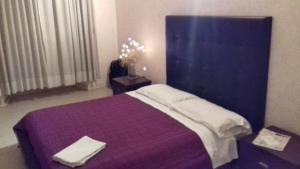 A bed or beds in a room at H.H
