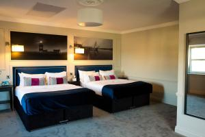 A bed or beds in a room at Kennedy Boutique Hotel
