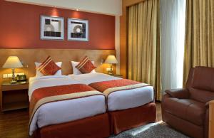 A bed or beds in a room at Savoy Suites Manesar