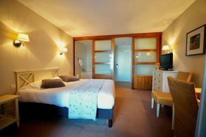 A bed or beds in a room at Clos de Vallombreuse, The Originals Relais (Relais du Silence)