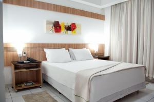 A bed or beds in a room at Delcas Hotel