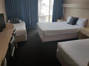 A bed or beds in a room at Acacia Motel